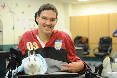 Individual holds a bunny rabbit.